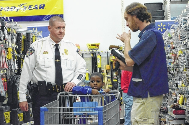 eddie grant and 6 year old jeremy lindsey talk with walmart associate brandon chance in the hardware department to try to find a gift for lindseys father