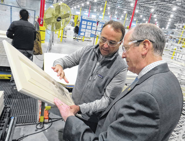 Gavin Stone | Daily Journal Bob Young, director of operations for the American Woodmark plant in the Richmond County Industrial Park, shows Congressman Dan Bishop a cabinet panel near the end of their assembly line.