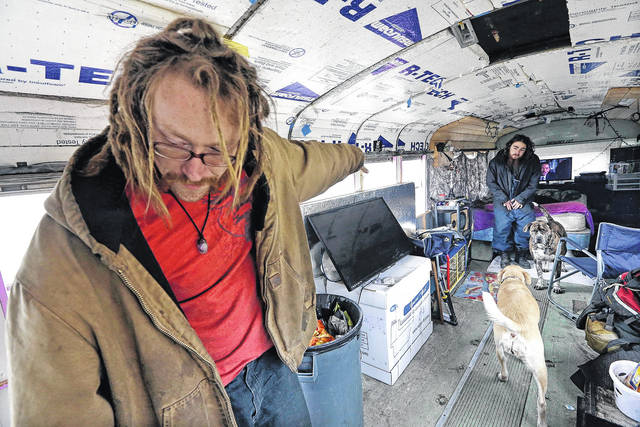 """Danny Fletcher, left, calls to his dogs as Joshua Madrid looks on in an old bus they share with three dogs in a temporary city-approved parking area for people living in their vehicles in Seattle. Fletcher, 32, who sleeps in his car at night, prefers the quiet of the parking zone to the harassment he faced in other parts of the city. """"We just want a safe place. Give us a safe place to park where neighbors won't harass us,"""" he said. """"We're homeless. We're not diseased."""" (AP Photo/Elaine Thompson) ORG XMIT: NY704"""