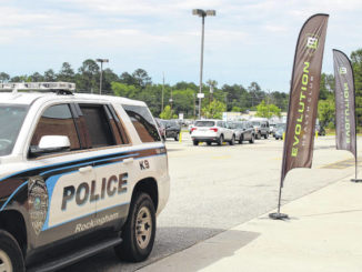 Gavin Stone | Daily Journal                                 A Rockingham police vehicle sits outside Evolution Health Club Friday while an officer speaks to Blake Altman, the owner.