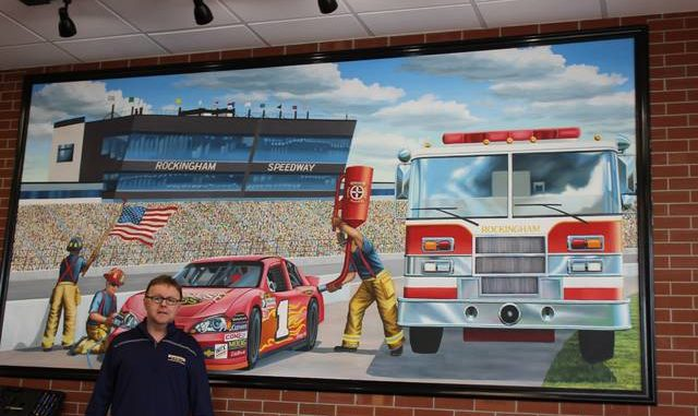 Brandon Tester | Daily Journal                                 Rockingham Firehouse Subs franchisee Larry Chandler stands in front of a mural of Rockingham Speedway that is on display in the new restaurant. Joe Puskas painted the mural. Puskas produces murals for all of the Firehouse Subs locations around the nation.