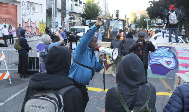 AP Photo | Ted S. Warren                                 A man speaking in to a bullhorn urges protesters not to be violent after workers and heavy equipment from the Seattle Department of Transportation arrived at the the CHOP (Capitol Hill Occupied Protest) zone in Seattle on Friday with the intention of removing barricades that had been set up in the area.