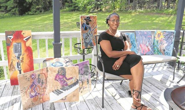 Renee Harden sits with a series of her jazz paintings.