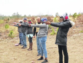 Daily Journal file photo                                 Robert Heaton, center, coaches students on proper stance and grip as they complete the shooting proficiency exam to obtain their concealed carry handgun permits in 2019.