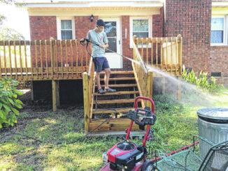 J.A. Bolton's grandson power washes a porch.                                  Photo courtesy of J.A. Bolton