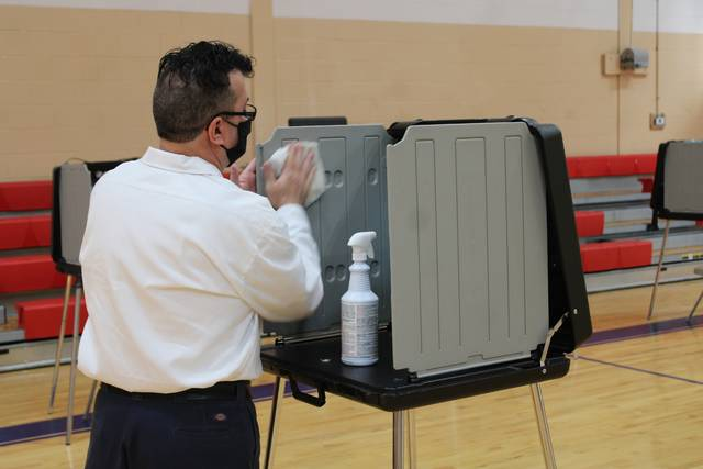 Gavin Stone | Daily Journal                                 Poll worker Michael Griffin cleans the polling stations in between uses by voters.