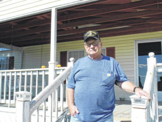 Freddie Sellers poses as his home in Lilesville.