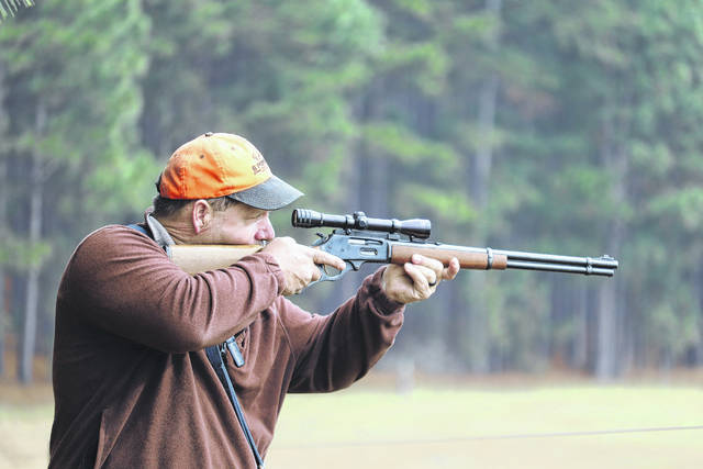 Clint Smith takes aim with his rifle at a deer off in a field in the distance.                                  Neel Madhavan | Daily Journal