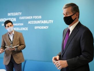 AP Photo | Gerry Broome                                 Gov. Roy Cooper, right, is seen during a visit to Gilero in Pittsboro, N.C., Thursday, Dec. 3, 2020. The medical device manufacturer began producing face shields when the pandemic started and also produces swabs for rapid tests in addition to self contained oxygenated negative pressure environments.