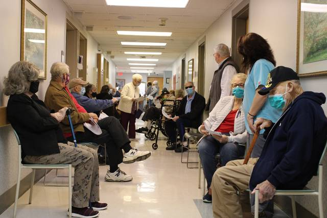 Gavin Stone | Daily Journal                                 Seniors who have received their first dose of the Moderna vaccine at FirstHealth on Monday wait in the hallway while socially distanced for 15 minutes to be sure that they aren't having any immediate negative reaction to the vaccine.
