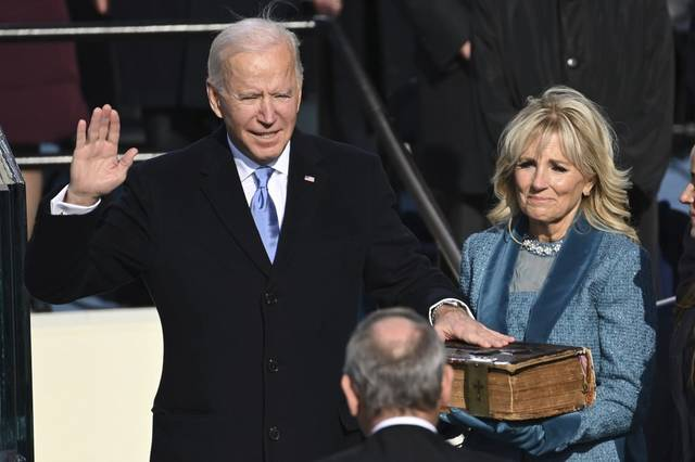 Saul Loeb | Pool Photo via AP                                 Joe Biden is sworn in as the 46th president of the United States by Chief Justice John Roberts as Jill Biden holds the Bible during the 59th Presidential Inauguration at the U.S. Capitol in Washington, Wednesday, Jan. 20, 2021.