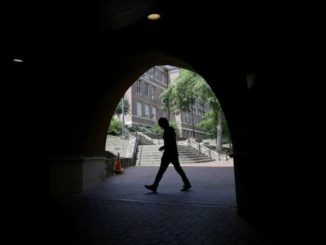 AP Photo | Gerry Broome                                 A pedestrian uses a tunnel walkway at the University of North Carolina in Chapel Hill, N.C., Tuesday, June 30, 2020.