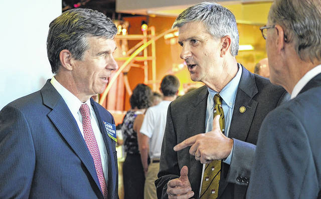 Daily Journal file photo                                 Then-Attorney General Roy Cooper speaks with then-Sen. Gene McLaurin during a 2014 campaign event at Discovery Place Kids in Rockingham. Cooper appointed McLaurin to the Economic Development Partnership of North Carolina on Tuesday.