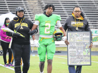 Senior Dalton Stroman Jr. and his parents Janet and Dalton Sr., walk across the field at Raider Stadium during the team's Senior Day ceremony.                                  Neel Madhavan | Daily Journal File Photos