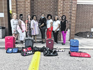 SOUL Stand Up members pose with the suitcases they acquired through a fundraiser to support children in foster care.