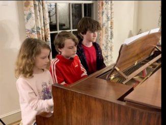 Photo courtesy of John Hutchinson                                 John Patrick, Alexander, and Evelyn Hutchinson sit at their piano.