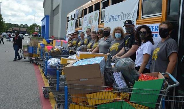 Volunteers for the 12th annual Stuff the Bus supply drive pose in front of Walmart with shopping carts full of school supplies.  The event is a partnership between the Richmond County Schools, the United Way of Richmond County and Walmart to raise funds for the purchase of school supplies through corporate sponsorship.  The materials are distributed to school system staff as needed.