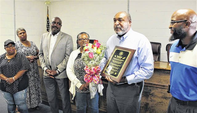 Gavin Stone   Daily Journal                                 Dennis Quick, center, accepts a plaque and bouquet of flowers from the Dobbins Heights Town Council on Thursday. Pictured are, from left, Councilwoman Angeline David, Councilwoman Mary Ann Gibson, Mayor Antonio Blue, Councilwoman Revonna Magee, Quick, and Mayor Pro Tem Tyre Holloway.