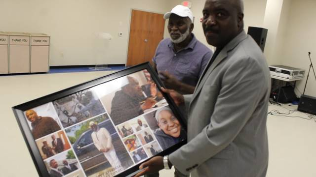 Dobbins Heights mayor Antonio Blue shows off the photo collage presented to him in honor of his service to the town.                                  Gavin Stone | Daily Journal