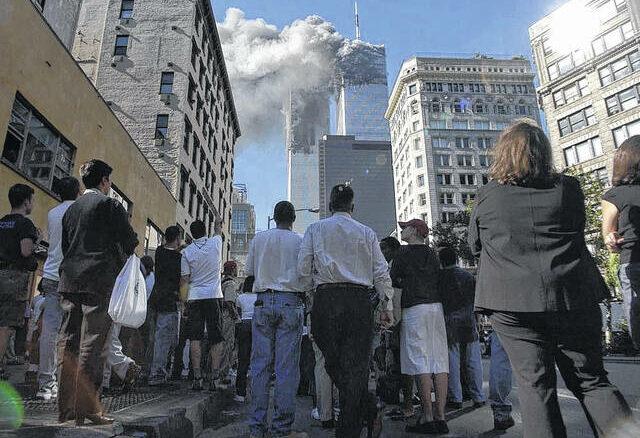 AP Photo   Amy Sancetta                                 Pedestrians in lower Manhattan watch smoke billow from New York's World Trade Center on Tuesday, Sept. 11, 2001.