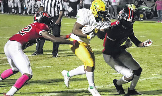 Junior running back Taye Spencer (21) runs through two defenders on Friday night against Hoke County on his way to the end zone.  Neel Madhavan Staff Writer